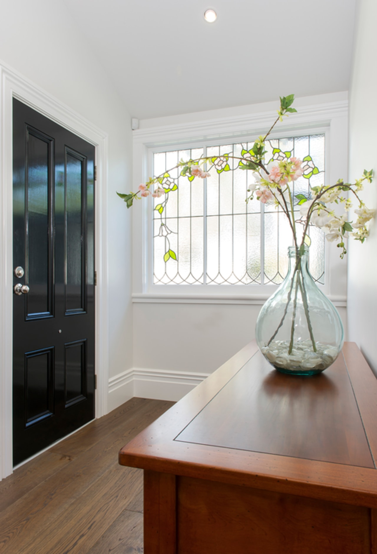 Glossy paint used on the front door reflects apartment, floor, home, house, interior design, room, table, window, wood, gray, white