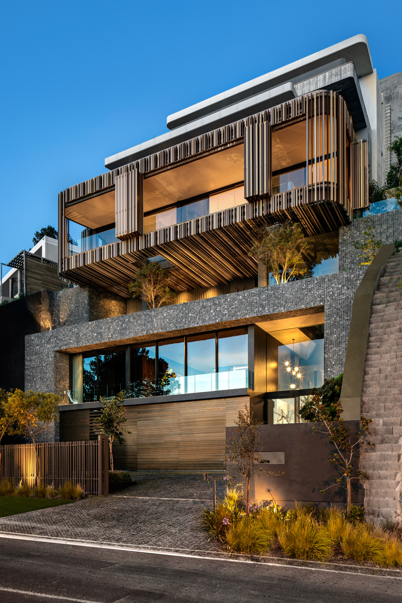 The home was conceived as an arrangement of apartment, architecture, building, estate, facade, home, house, interior design, mixed-use, property, real estate, residential area, sky, tree, black