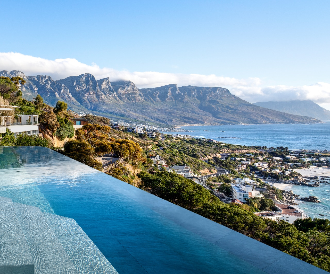 The infinity edge pool enhances to the mountain azure, bay, blue, caribbean, coast, coastal and oceanic landforms, hill, house, landscape, leisure, mountain, mountain range, natural landscape, ocean, promontory, real estate, resort, resort town, sea, shore, sky, swimming pool, tourism, tropics, vacation, water, teal, white