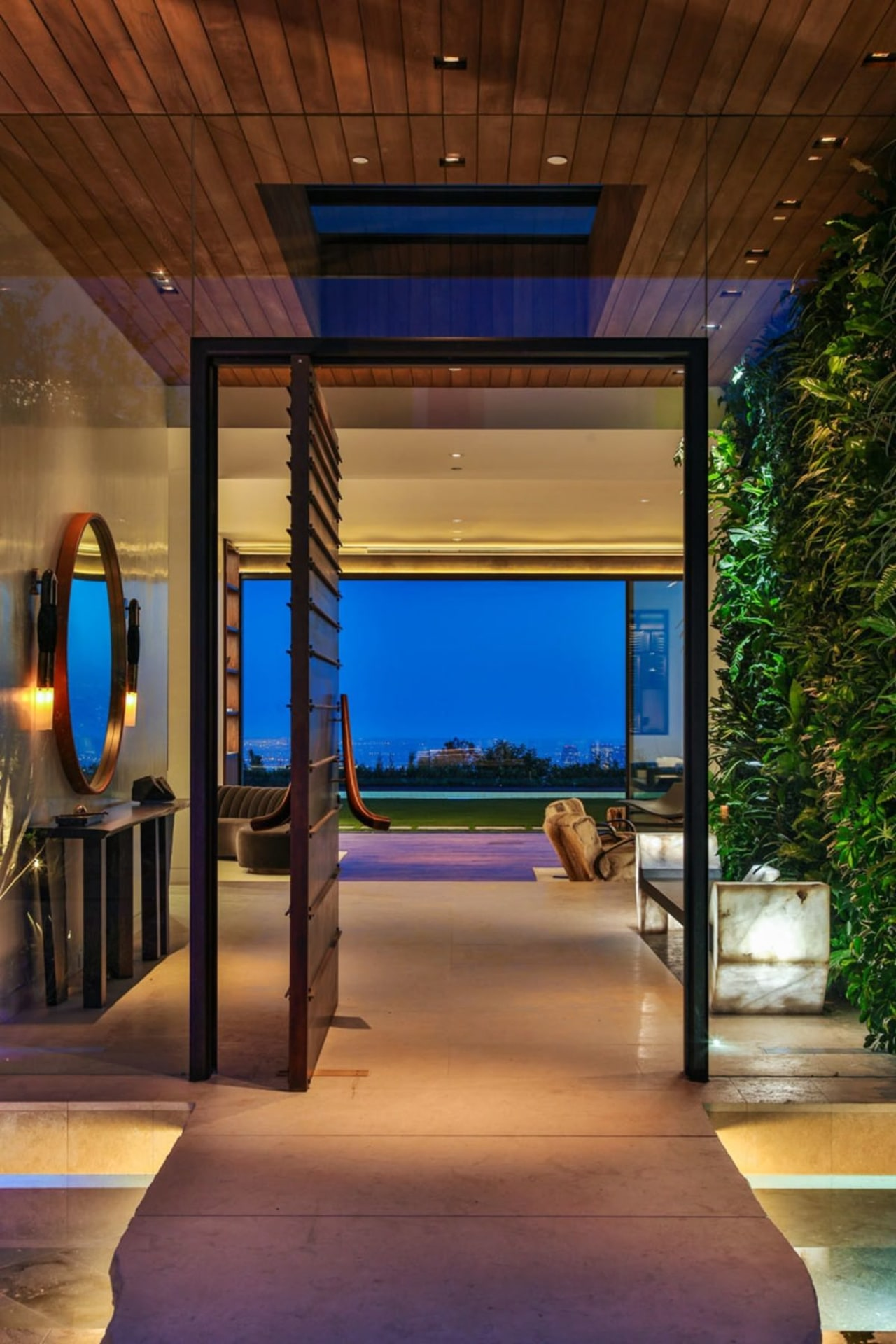 A large pivoting wooden door welcomes you architecture, ceiling, estate, home, house, interior design, lighting, real estate, brown
