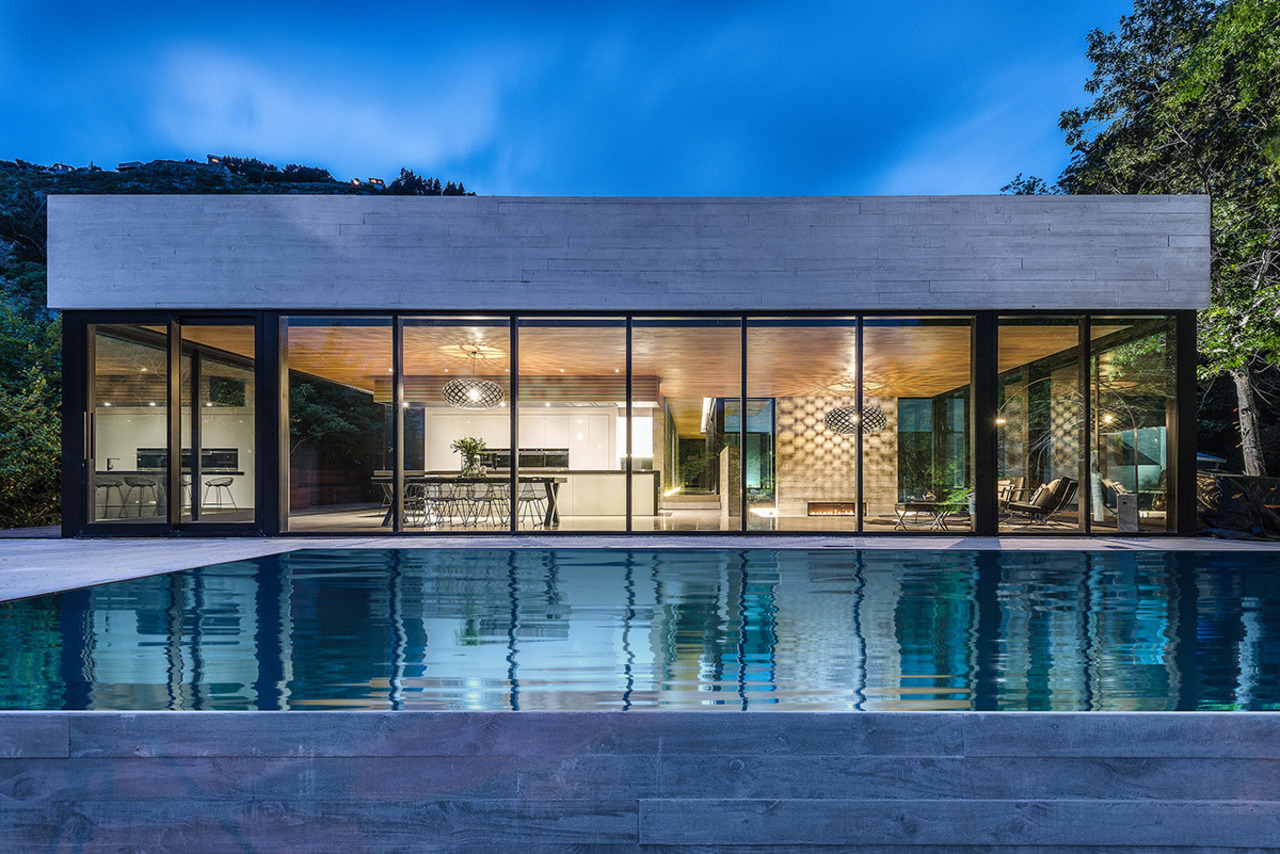 Seen from across the pool, this kitchen's strong, architecture, corporate headquarters, estate, facade, home, house, property, real estate, reflection, residential area, sky, swimming pool, villa, water, window, blue