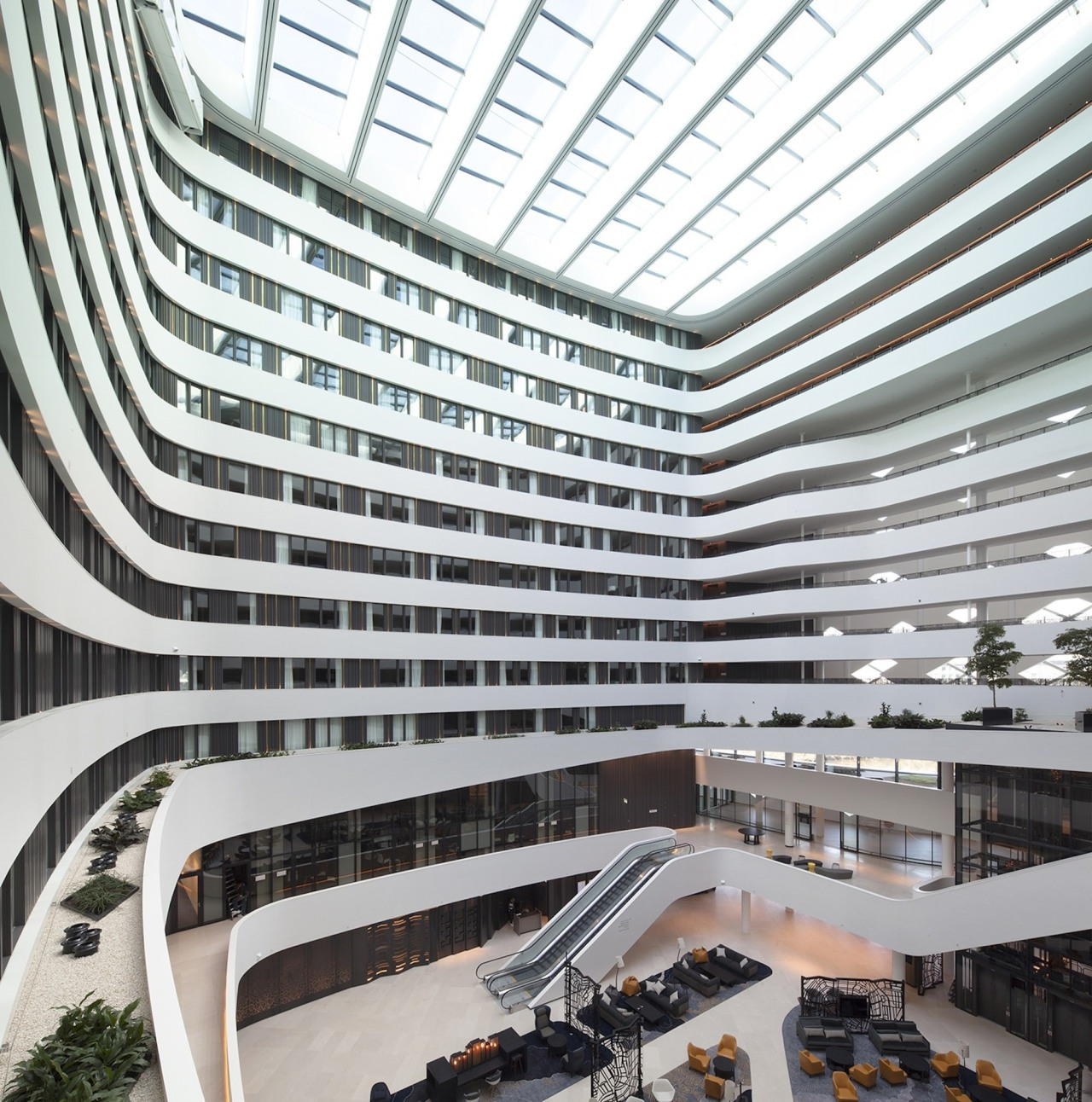 The lobby features a seriously impressive skylight architecture, building, commercial building, corporate headquarters, daylighting, headquarters, metropolis, metropolitan area, mixed use, shopping mall, white, gray