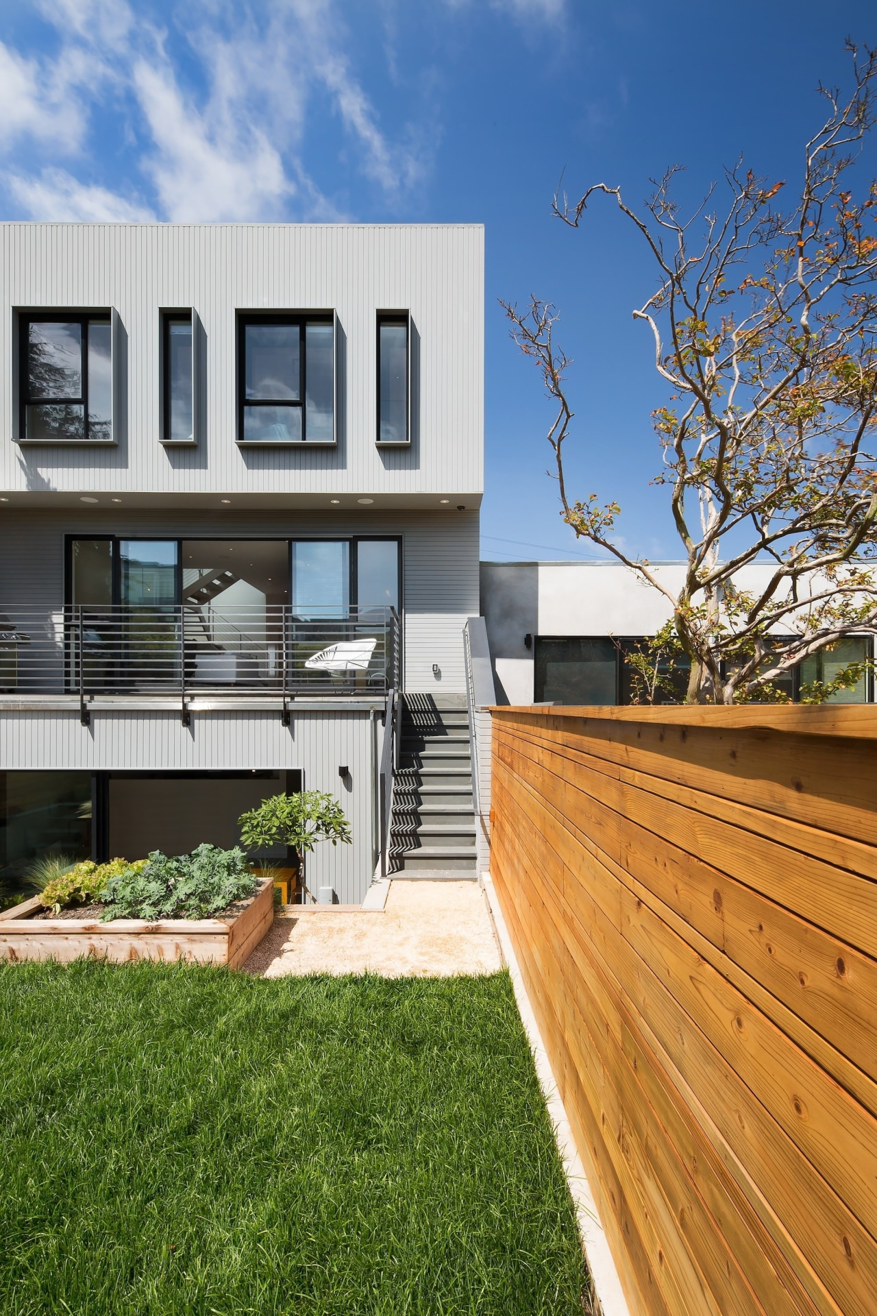 A timber boundary fence contrasts with the home apartment, architecture, backyard, balcony, deck, estate, facade, grass, home, house, neighbourhood, outdoor structure, property, real estate, residential area, siding, wood, yard