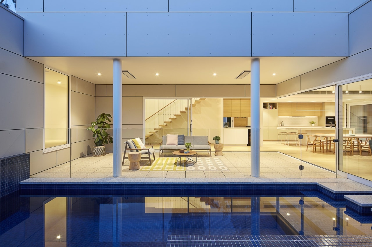 The serene pool sits alongside a sheltered outdoor apartment, architecture, condominium, estate, home, house, interior design, leisure centre, property, real estate, orange