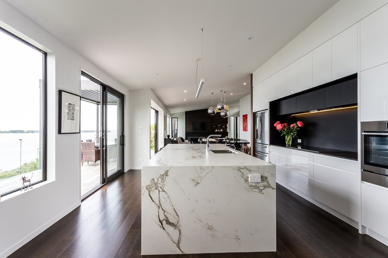 The kitchen features large windows, wood floors and architecture, countertop, house, interior design, kitchen, living room, real estate, gray