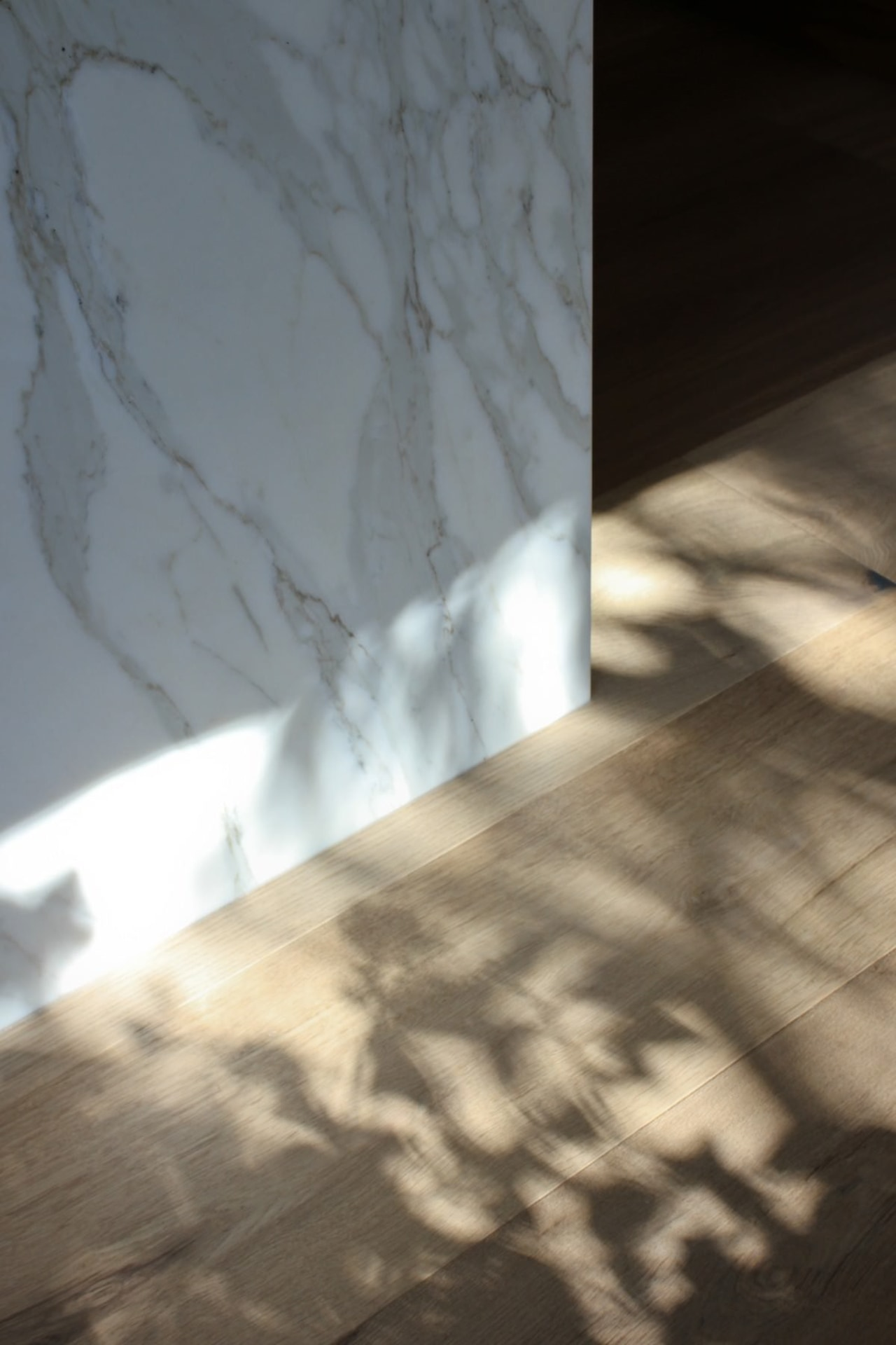 A close-up of where the island counter meets angle, atmosphere, daylighting, floor, light, line, reflection, shadow, sky, sunlight, texture, wall, wood, gray, brown