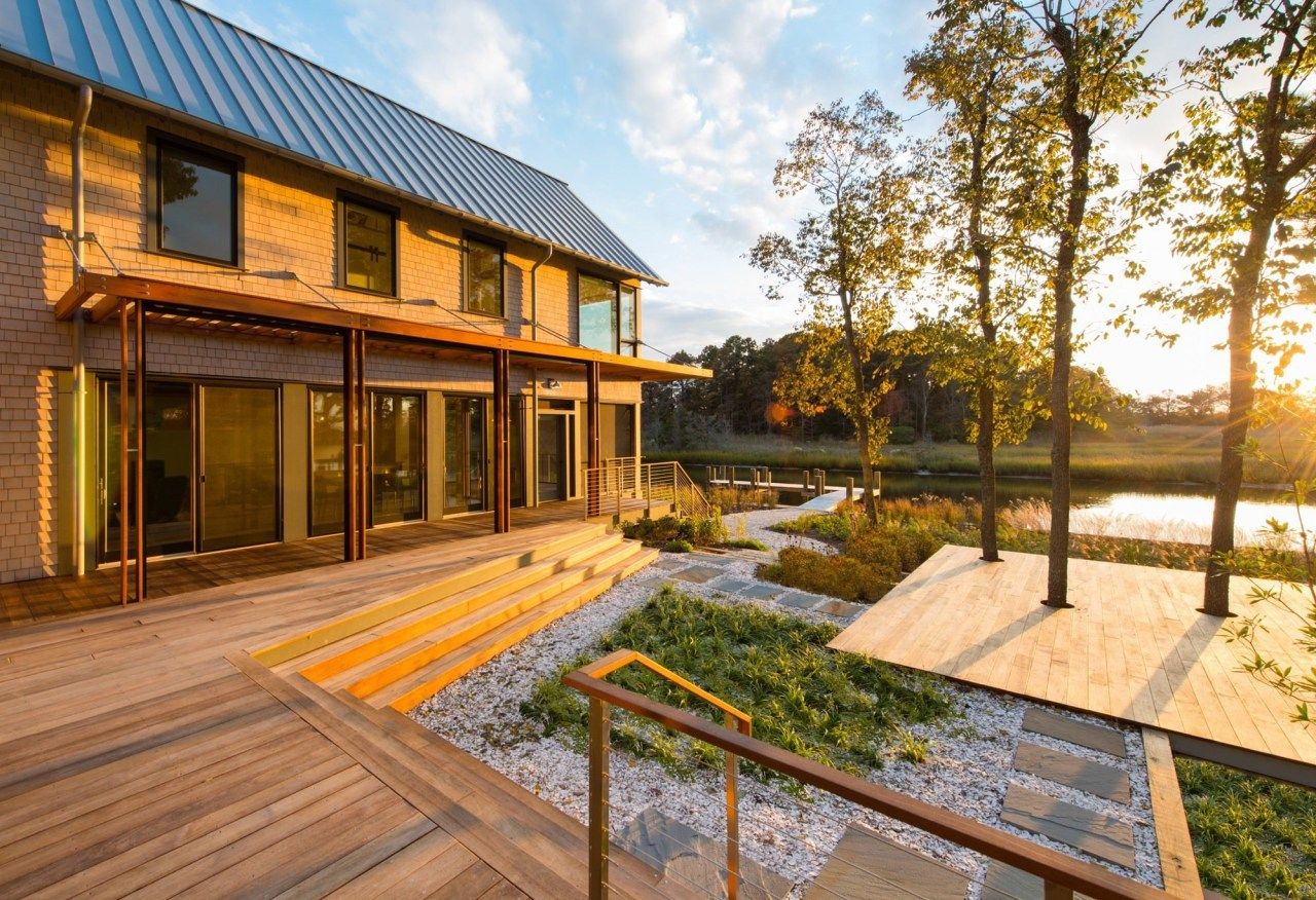 It's clear the home design has been influenced architecture, backyard, cottage, courtyard, deck, estate, facade, home, house, outdoor structure, property, real estate, residential area, siding, brown