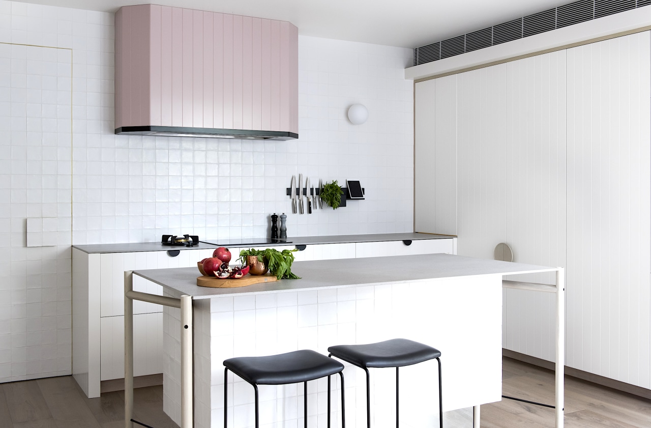 A light pink rangehood provides a quiet feature white