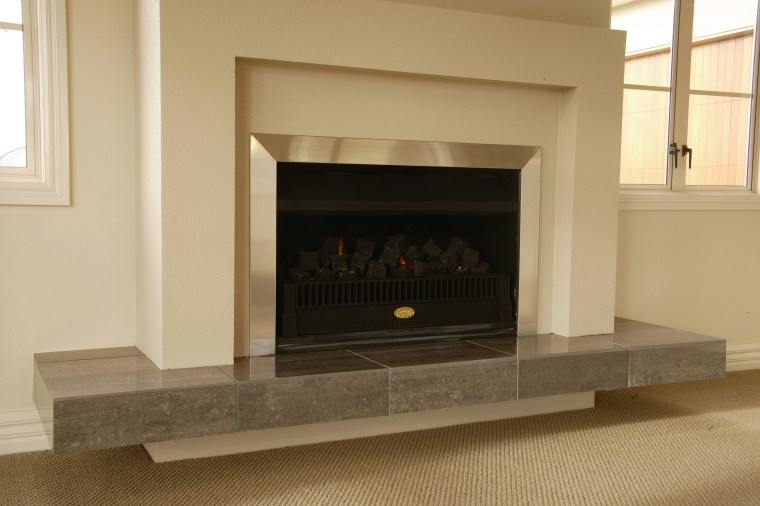 Fire in cream fireplace with stainless steel surround fireplace, flooring, hearth, wood burning stove, orange, brown
