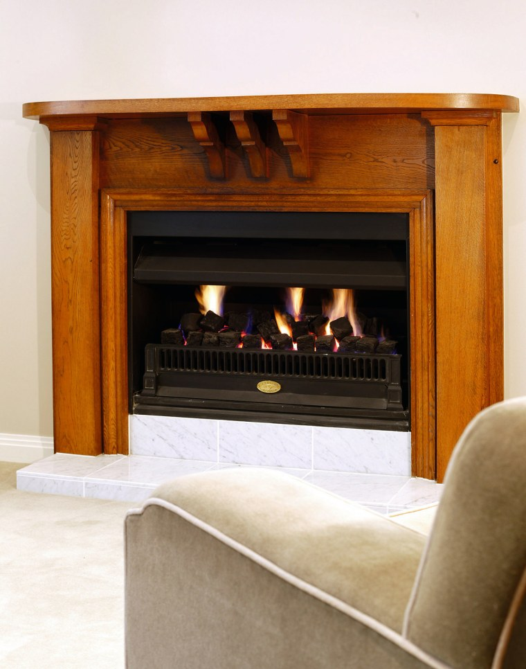 A fireplace with a wooden surround.  There fireplace, furniture, hearth, heat, wood burning stove, white, brown