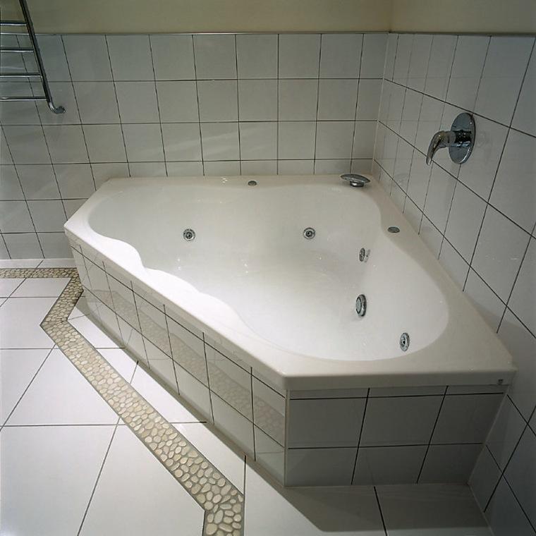 A spa bath fitted into the corner of bathroom, bathroom sink, bathtub, floor, flooring, plumbing fixture, product design, property, sink, tile, wall, gray