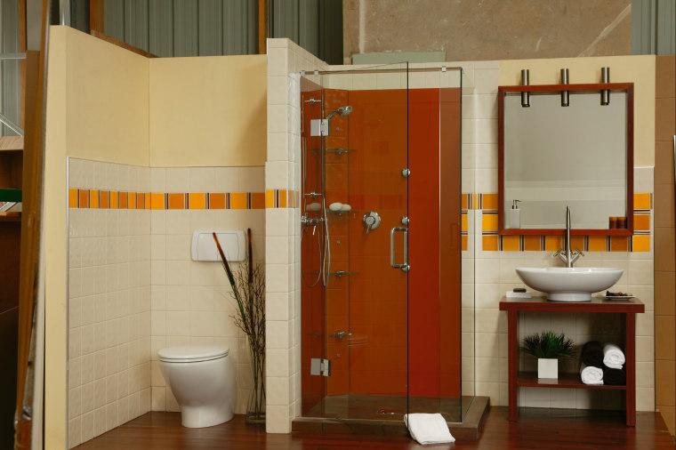 A bathroom featuring an orange coloured glass shower. bathroom, bathroom accessory, floor, interior design, plumbing fixture, room, toilet, brown, orange