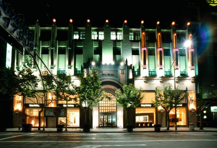 An exterior view of the large three storey architecture, building, city, condominium, downtown, facade, hotel, landmark, lighting, metropolis, metropolitan area, mixed use, night, black