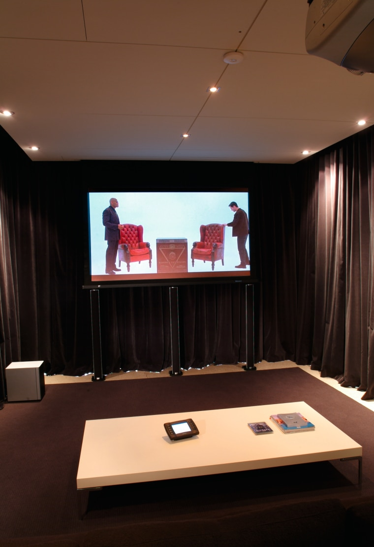 view of the home theatre area with motorised ceiling, conference hall, display device, furniture, interior design, room, table, black, brown
