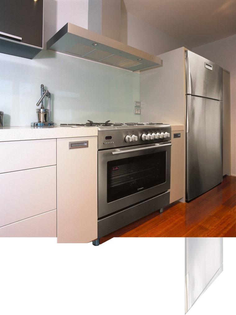 A view of a kitchen area, wooden flooring, cabinetry, countertop, gas stove, home appliance, kitchen, kitchen appliance, kitchen stove, major appliance, microwave oven, oven, small appliance, white