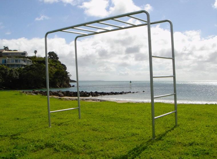 Outdoor tubular steel playground equipment. grass, land lot, structure, white, brown