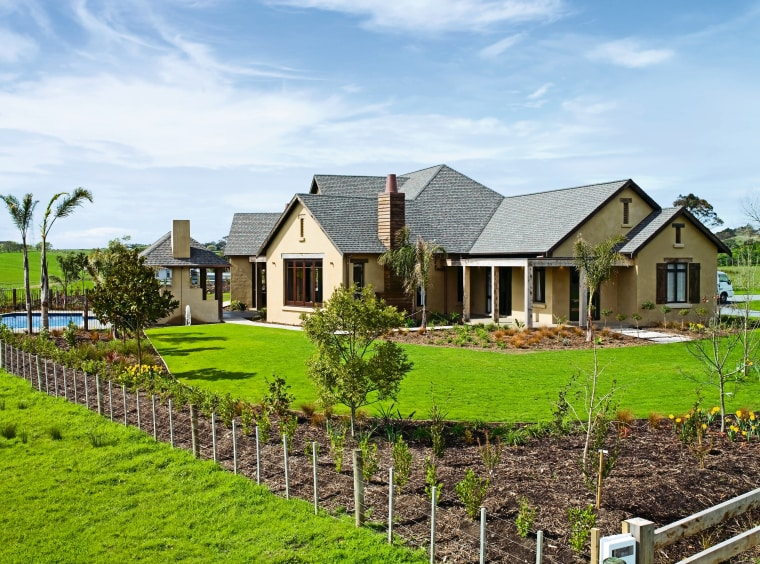 view of the house featuring plastered and lime cottage, estate, facade, farm, farmhouse, fence, field, grass, home, house, land lot, landscape, landscaping, lawn, outdoor structure, plantation, property, real estate, residential area, roof, rural area, sky, tree, yard, white