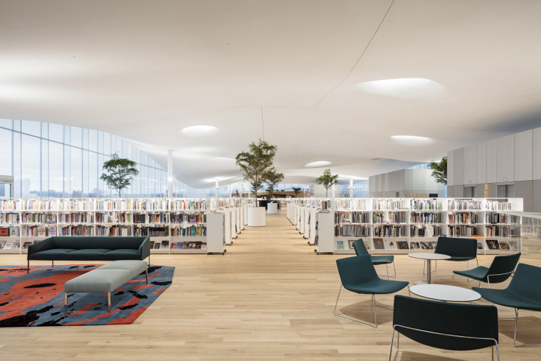 The innovative Helsinki library's structural design enables the architecture, building, ceiling, chair, design, floor, flooring, furniture, house, interior design, lobby, office, real estate, room, table, gray