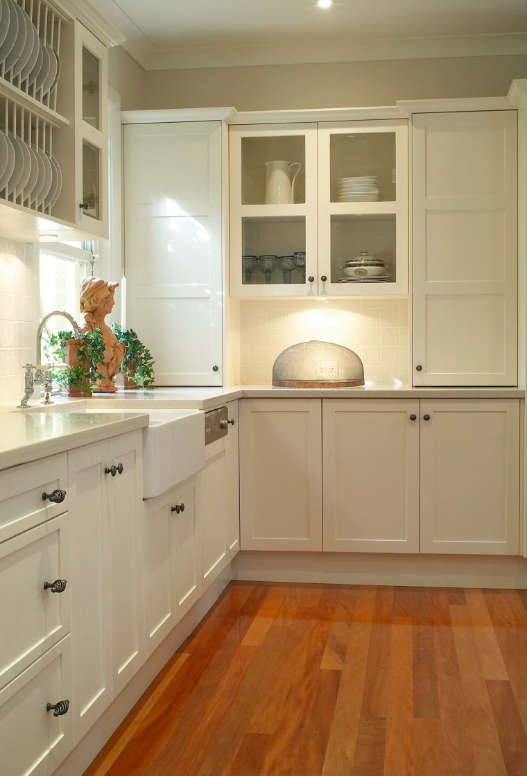 Kitchen with white cabinetry, metal handles, sunken sink, cabinetry, countertop, cuisine classique, floor, flooring, hardwood, home, home appliance, interior design, kitchen, laminate flooring, room, tile, wall, wood, wood flooring, wood stain, brown, orange