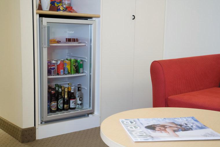 A view of a Haier mini fridge. furniture, home appliance, product, refrigerator, shelf, shelving, gray