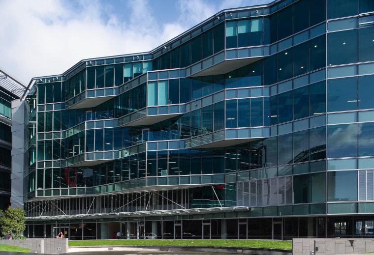 An exterior view of the Microsoft building. apartment, architecture, building, commercial building, condominium, corporate headquarters, daytime, facade, headquarters, metropolis, metropolitan area, mixed use, residential area, sky, blue, black