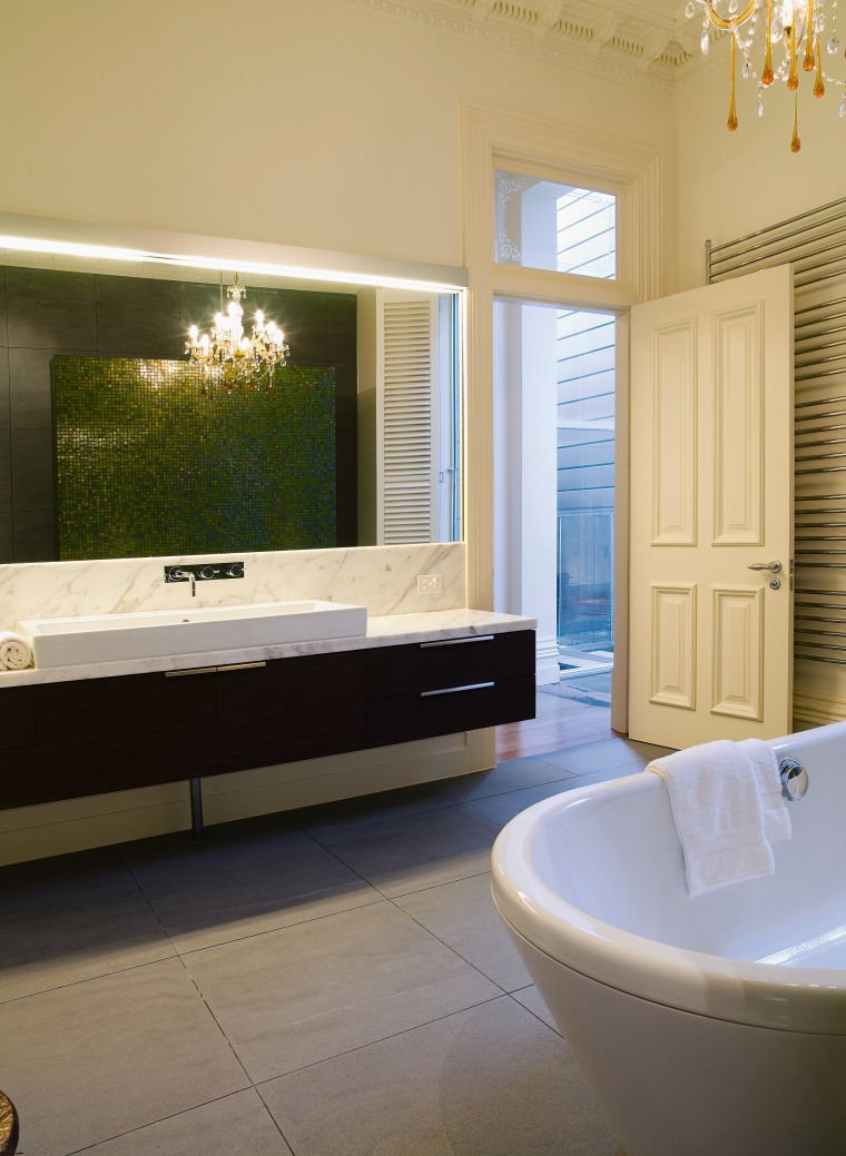 A wall-hung vanity is a contemporary feature that bathroom, bathtub, floor, flooring, home, interior design, room, window, orange