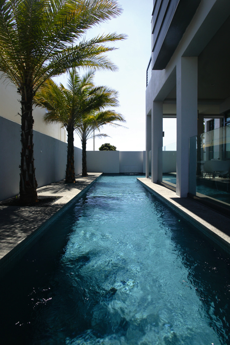 View of an L-shaped lap pool by Pool architecture, arecales, condominium, estate, home, house, palm tree, property, real estate, reflection, resort, sky, swimming pool, water, black