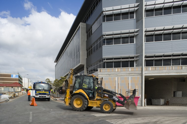 An exterior view of the Greensquare builing and asphalt, car, construction, construction equipment, mode of transport, motor vehicle, transport, vehicle, gray