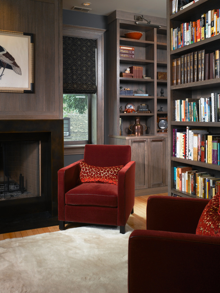 A view of this living area featuring red bookcase, floor, flooring, furniture, home, interior design, library, living room, shelf, shelving, black, gray