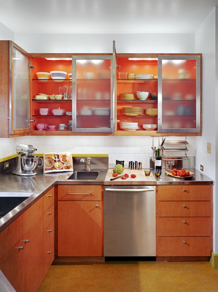 view of kitchen cabinetry, lightng, wooden flooring, sink, cabinetry, countertop, interior design, kitchen, orange, room, shelf, red