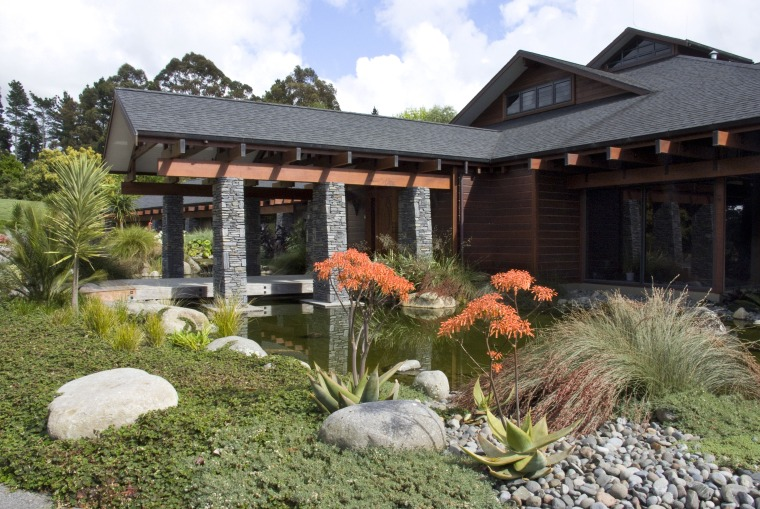 View of the entrance way which features schist backyard, cottage, estate, garden, home, house, landscape, landscaping, outdoor structure, plant, pond, property, real estate, yard