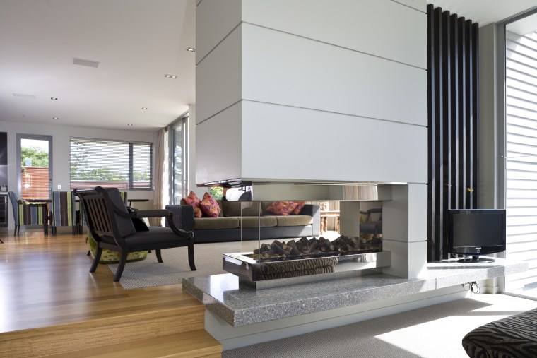 View of a living space with couches and fireplace, floor, hearth, house, interior design, living room, window, gray, white