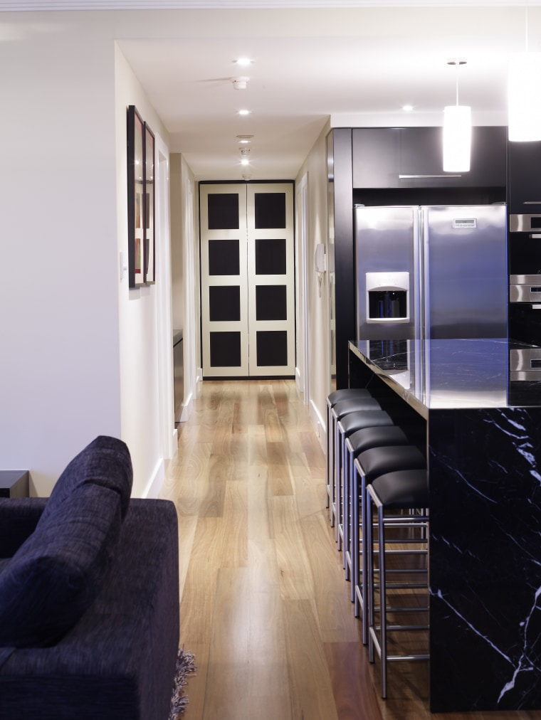View of an apartment kitchen which features solid floor, flooring, hardwood, interior design, laminate flooring, living room, room, wood, wood flooring, white, black