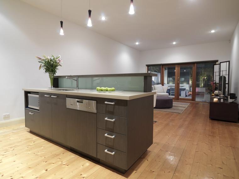 View of a kitchen featuring island, dark brown cabinetry, countertop, floor, flooring, hardwood, interior design, kitchen, real estate, room, gray, brown