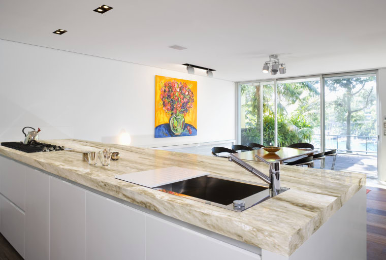 View of a kitchen island topped with a countertop, floor, interior design, kitchen, real estate, room, sink, gray