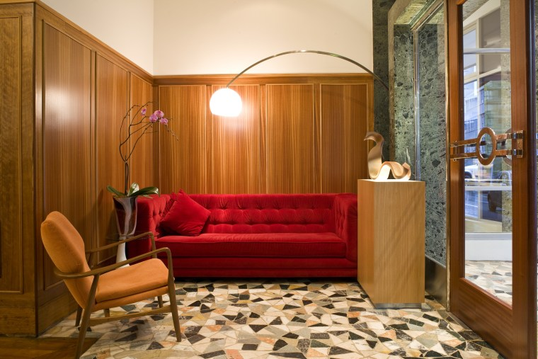 The entrance to this retro-themed hotel is finished floor, flooring, furniture, hardwood, home, interior design, living room, lobby, room, suite, brown, orange