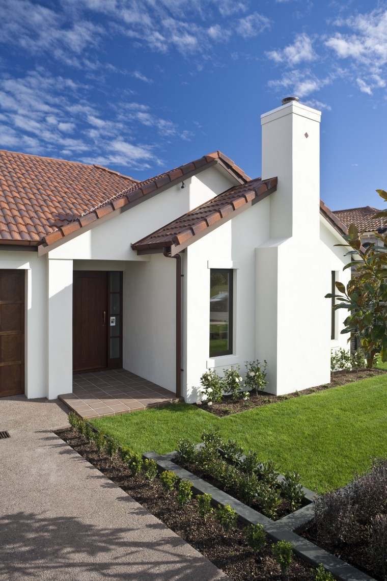 Exterior view of home featuring brick cladding, doors architecture, building, cottage, estate, facade, hacienda, home, house, property, real estate, residential area, roof, sky, villa, gray