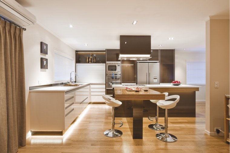 View of a kitchen which features island with cabinetry, countertop, cuisine classique, floor, furniture, interior design, kitchen, office, real estate, room, white, orange