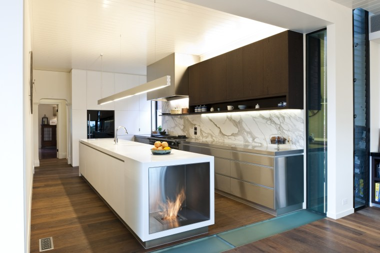 Fireplace built into island. Stainless steel appliances. Minimalistic cabinetry, countertop, cuisine classique, home appliance, interior design, kitchen, room, white