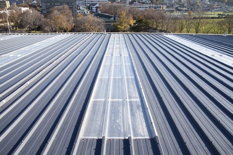 View of grey roof. architecture, asphalt, daylighting, daytime, line, outdoor structure, roof, sky, solar panel, solar power, gray