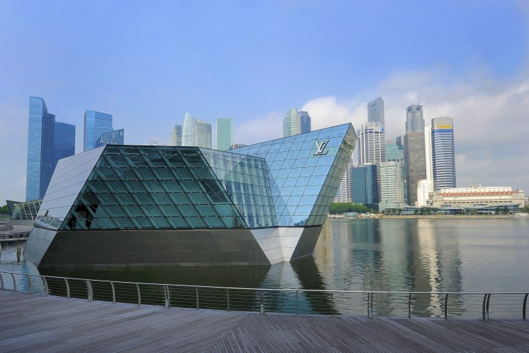 The Louis Vuitton Island Maison in Singapore appears architecture, building, city, cityscape, commercial building, condominium, corporate headquarters, daytime, downtown, fixed link, headquarters, landmark, metropolis, metropolitan area, mixed use, reflection, sky, skyline, skyscraper, tower block, urban area, water, teal, gray
