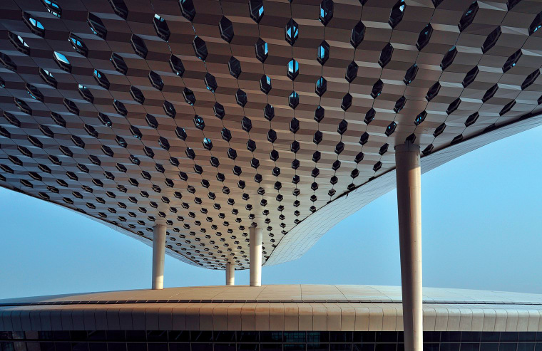 Looking much like a giant sculpture from both architecture, building, ceiling, daylighting, daytime, landmark, line, roof, sky, structure, symmetry, black