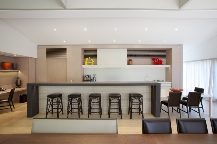 This kitchen's long island is extended further by ceiling, interior design, living room, table, gray