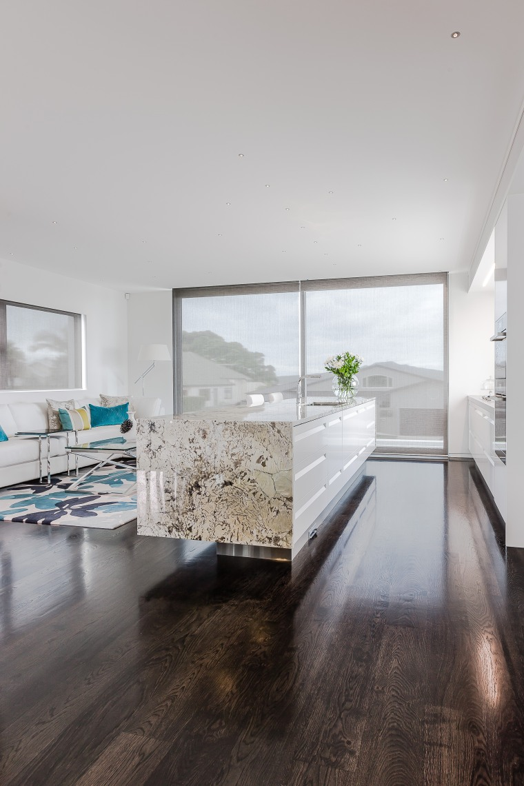 The island serves the owner's request for a apartment, architecture, ceiling, daylighting, floor, flooring, hardwood, home, house, interior design, laminate flooring, living room, wood, wood flooring, gray