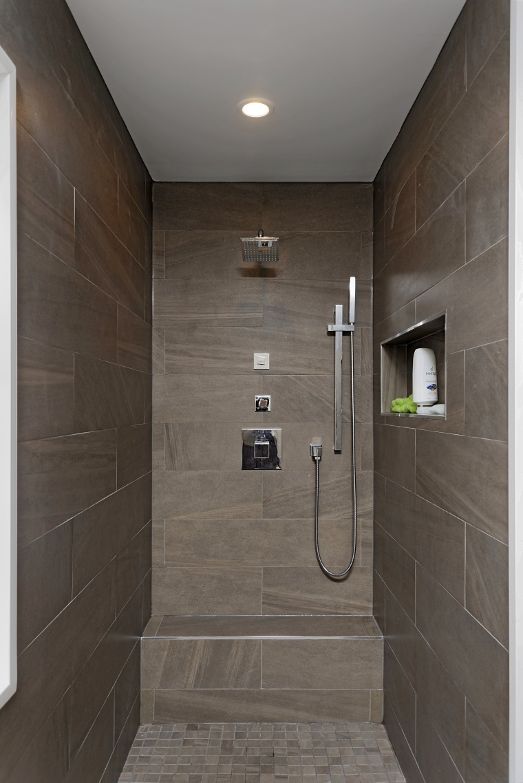 The two his and hers shower niches are bathroom, daylighting, floor, flooring, interior design, plumbing fixture, room, shower, tile, wall, gray, black