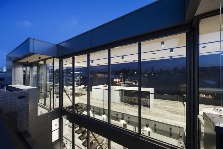 This long, narrow apartment rises above its industrial architecture, building, corporate headquarters, facade, real estate, window, black, blue