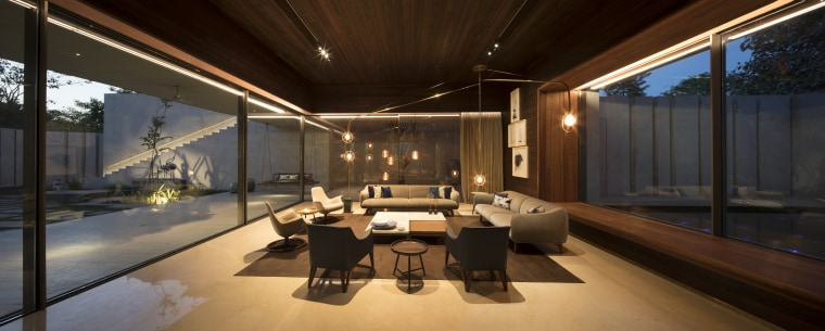 The dining area is situated in the longer architecture, building, ceiling, design, furniture, home, house, interior design, lighting, living room, property, real estate, room, black, brown
