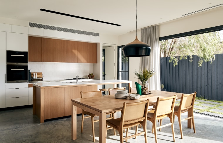 Indoors merge with outdoors in this user-friendly home. architecture, building, cabinetry, ceiling, countertop, cupboard, dining room, floor, flooring, furniture, hardwood, home, house, interior design, kitchen, kitchen stove, material property, plywood, property, real estate, room, table, wood, wood flooring, white