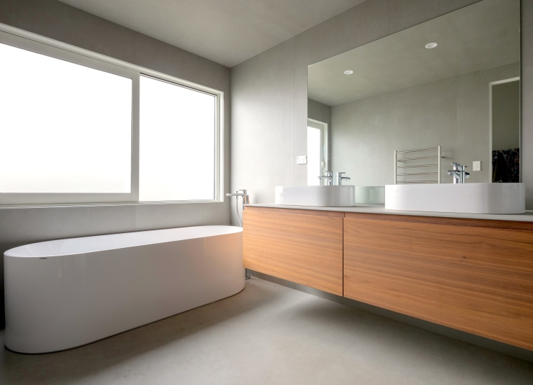 A clean-lined wall-hung vanity contrasts a curvaceous freestanding architecture, bathroom, building, cabinetry, ceiling, daylighting, floor, flooring, furniture, home, house, interior design, material property, property, real estate, room, sink, gray, white