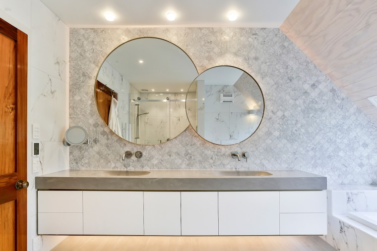 Two round mirrors are brought together in one architecture, bathroom, building, cabinetry, ceiling, countertop, floor, flooring, furniture, home, house, interior design, lighting, marble, property, real estate, room, sink, tap, tile, wall, gray